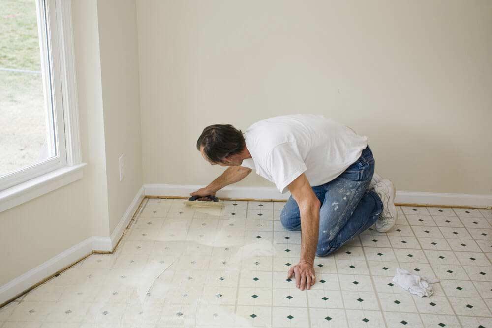 Un carreleur pose une sous-couche en vue de poser un nouveau revêtement de sol